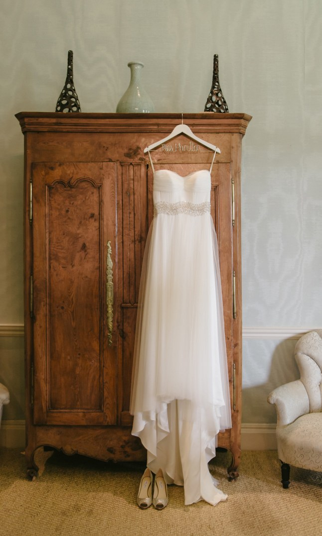 A wedding dress hanging on a wooden wardrobe.