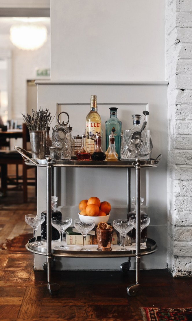 A drinks trolley containing bottles of alcohol and other cocktail ingredients.