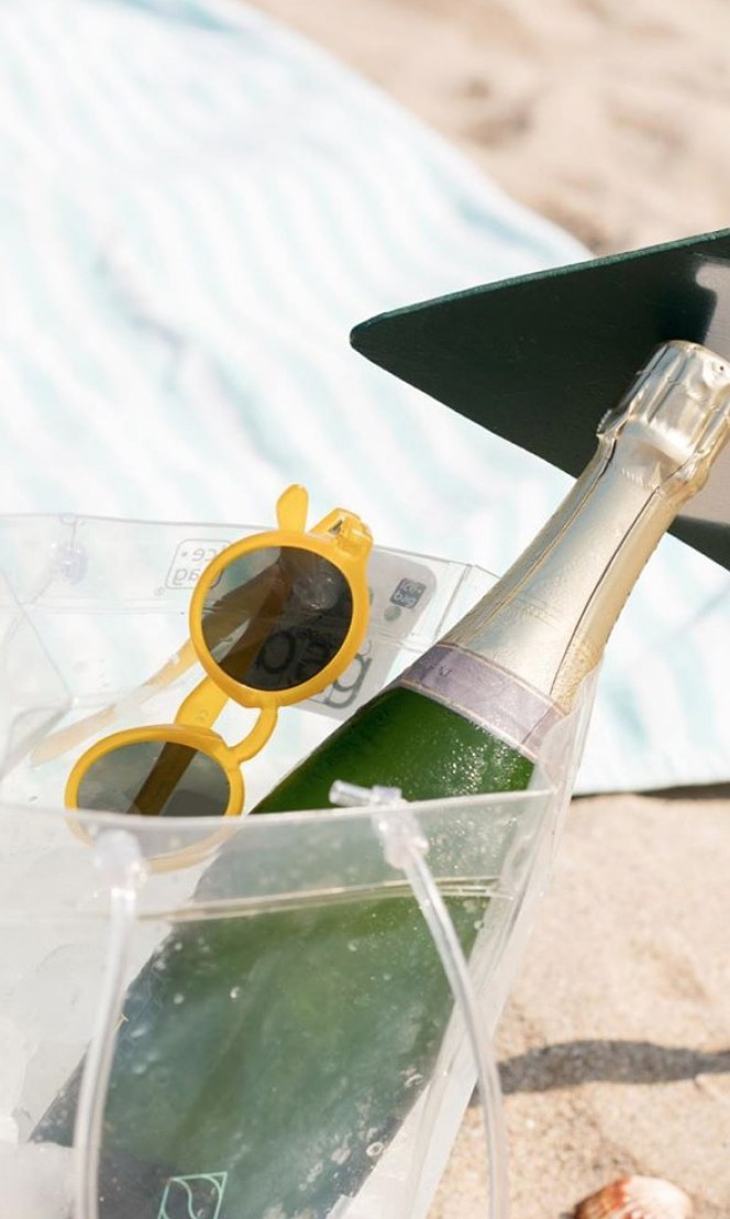 Sunglasses and champagne in a cooler on a beach.