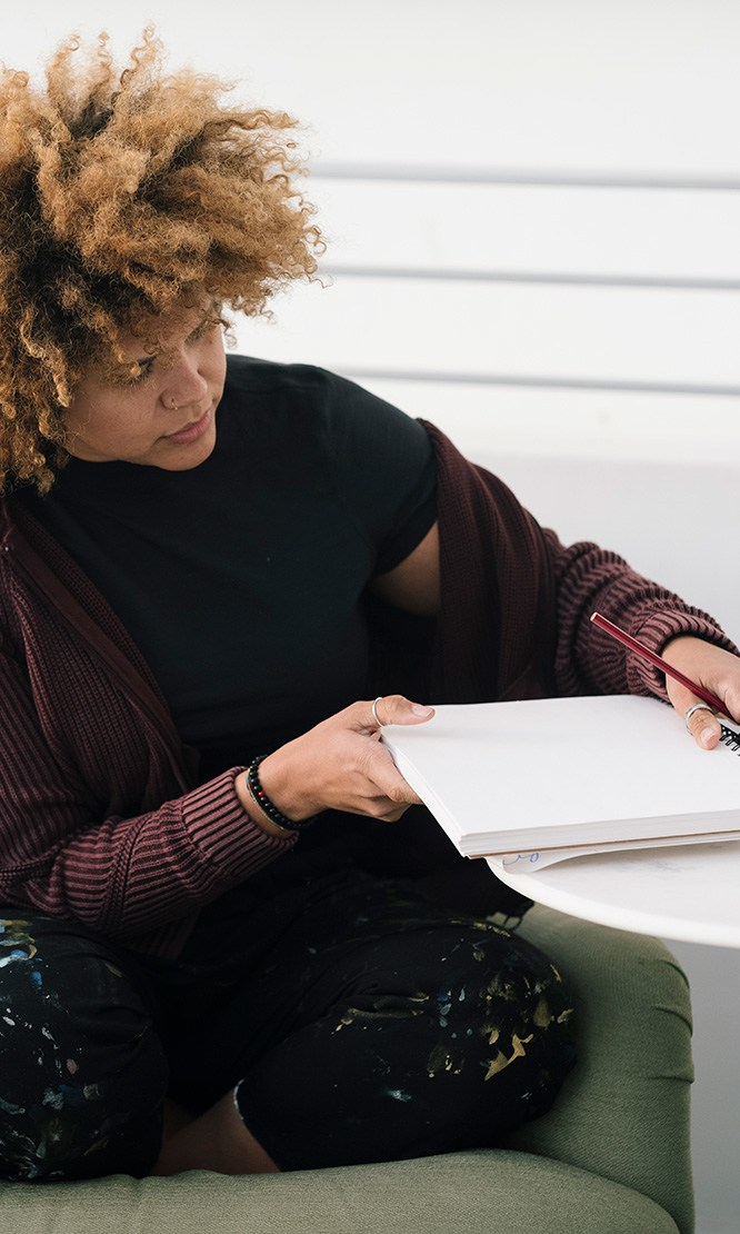 A woman writes in a notebook at a table.