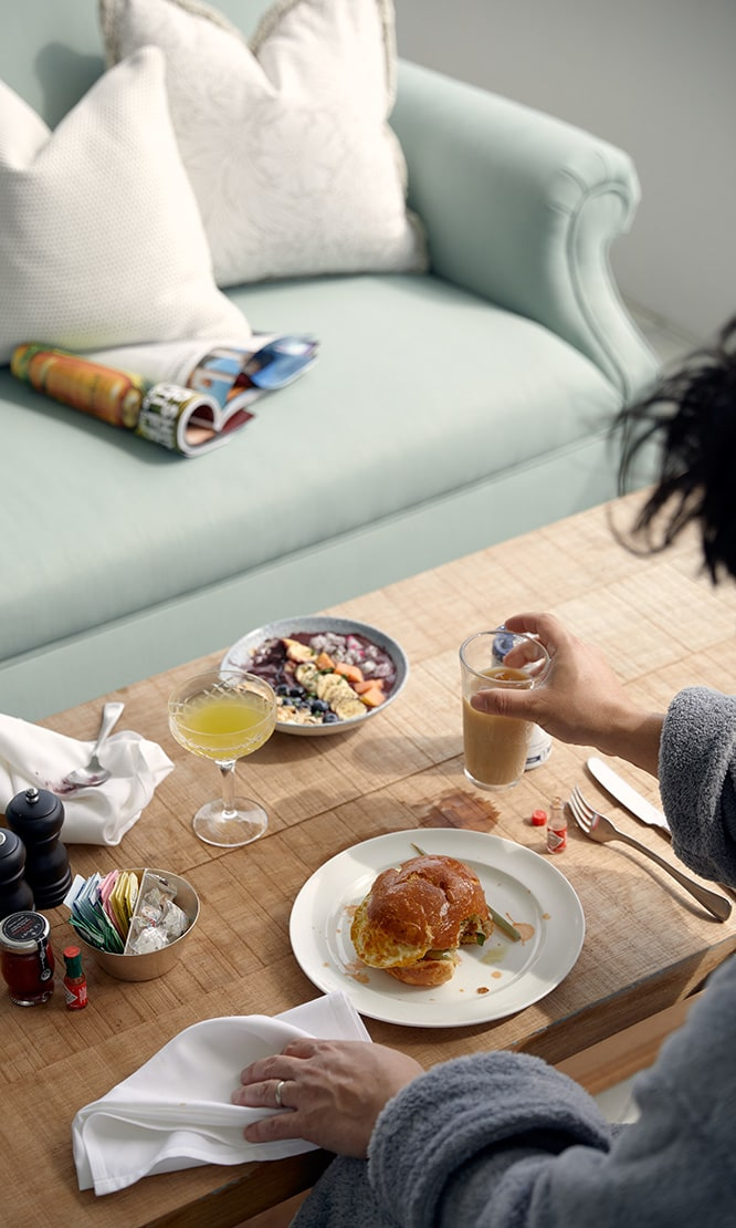 A person eating breakfast on a coffee table in their dressing gown.