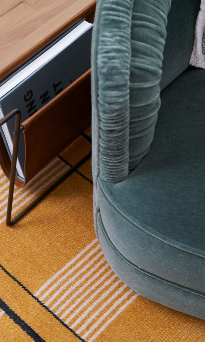 A closeup of a chair and a magazine holder.