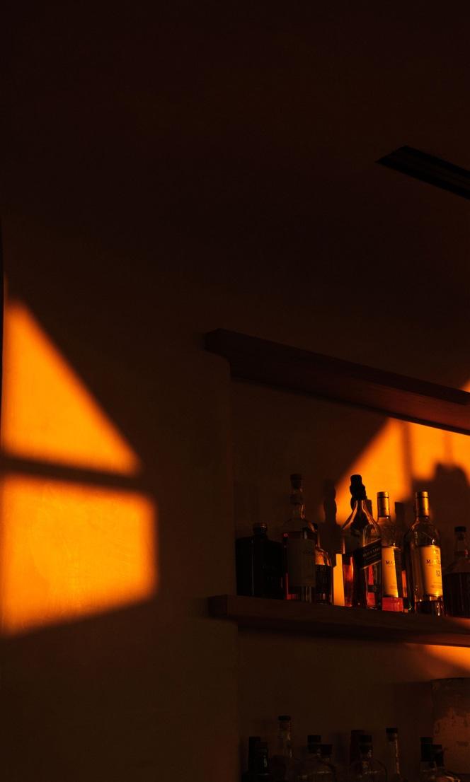 Light falls on a shelf of alcohol bottles.