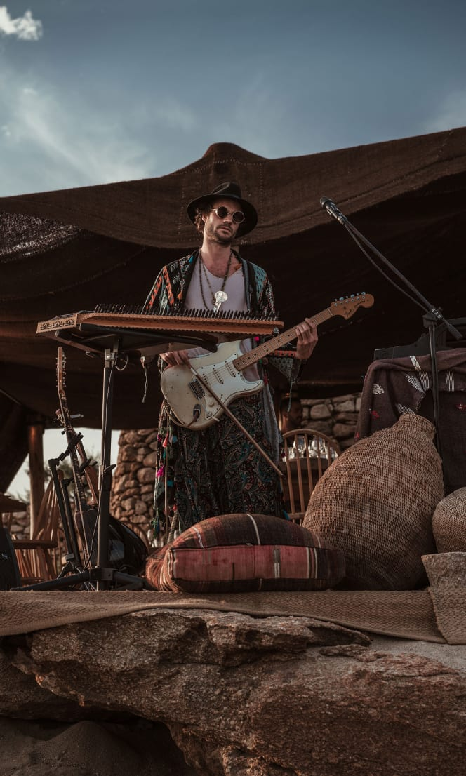 A man playing guitar on a makeshift beach stage.