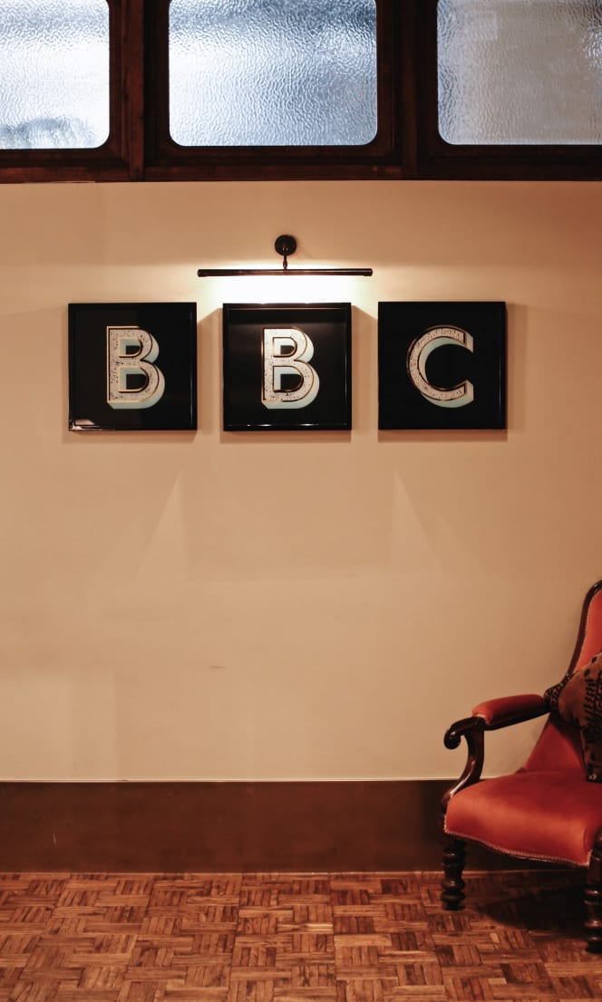 A BBC sign on a wall by a chair.