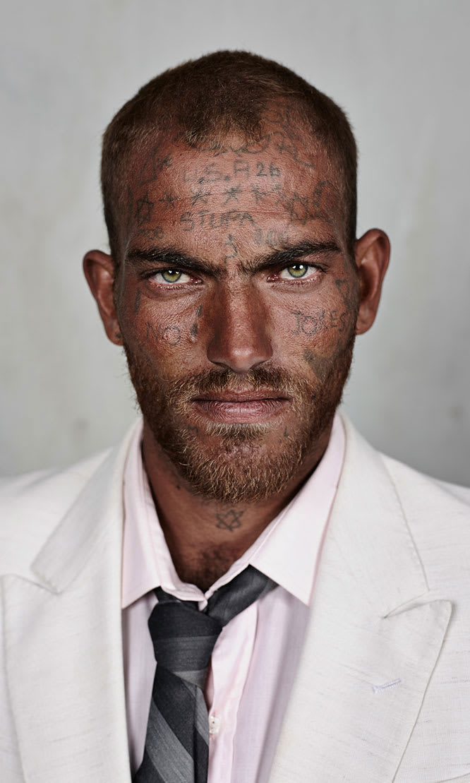 A man in a suit with writing on his face.