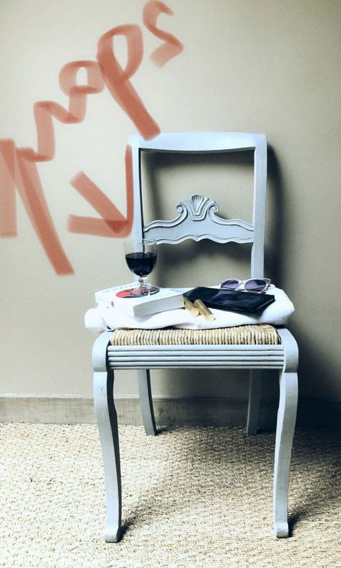 A chair with items on it and props written in red lipstick over it.