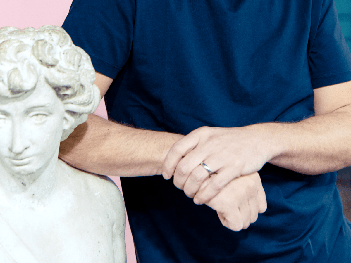 A man's crossed arms leaning on a bust sculpture