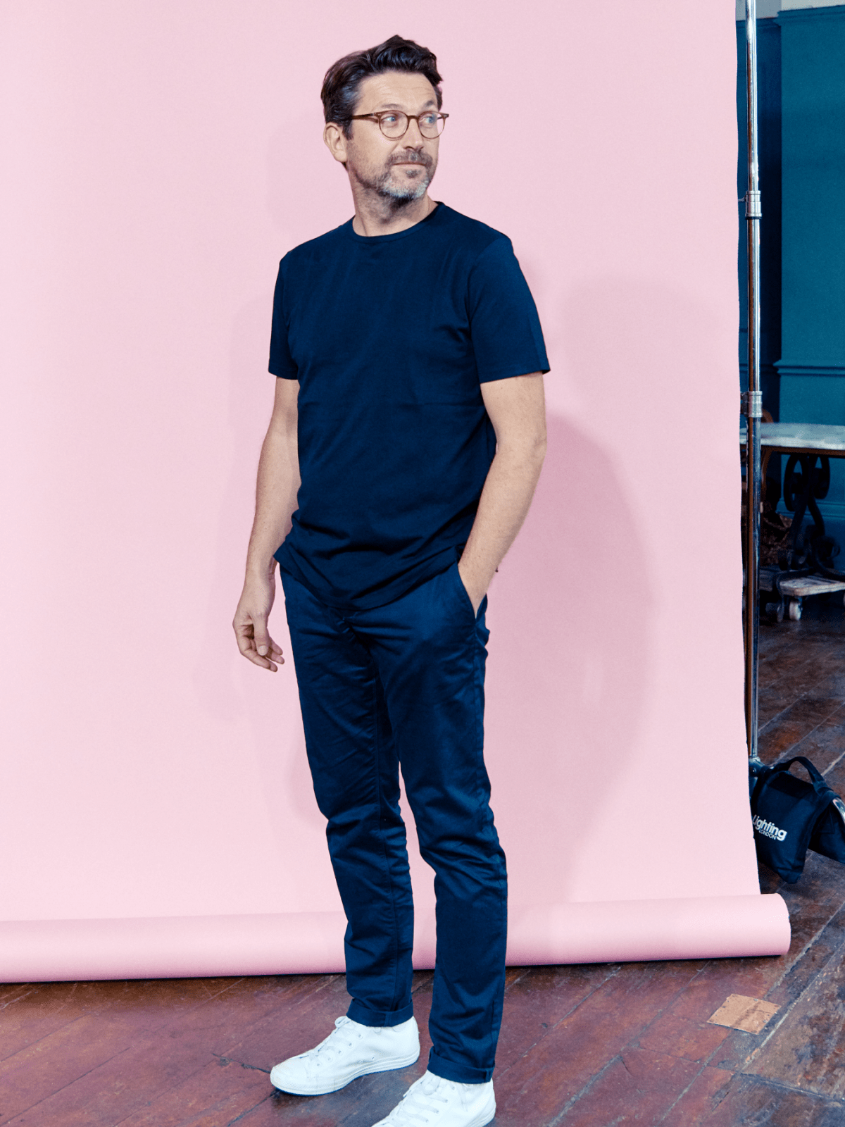 Man in blue t-shirt and trousers and sneakers standing relaxed