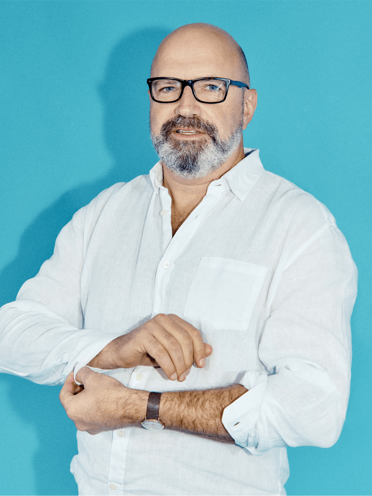 Man with beard and glasses doing up button on the cuff of shirt