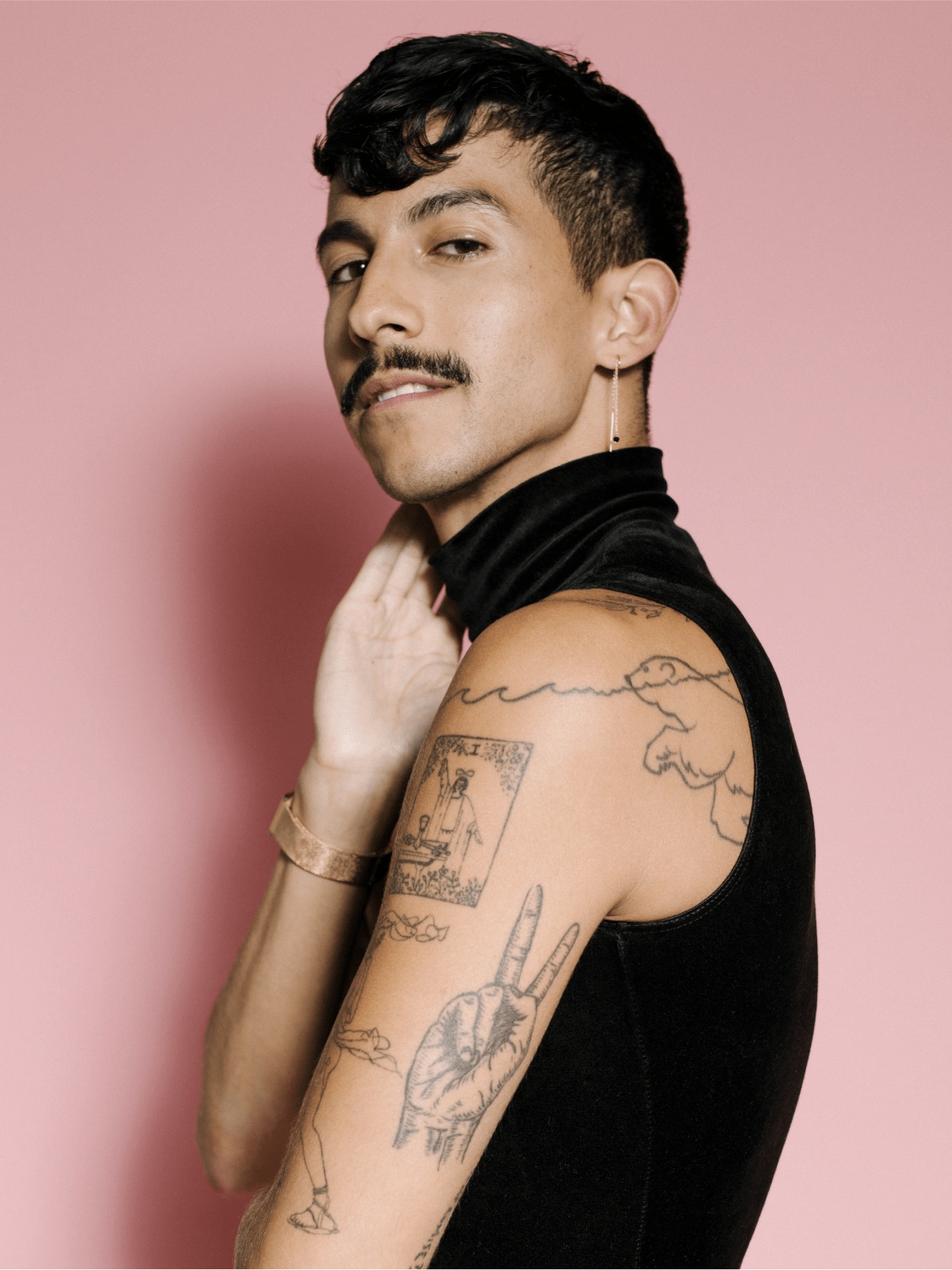 Man wearing sleeveless turtleneck and earings showing his arm with tattoos