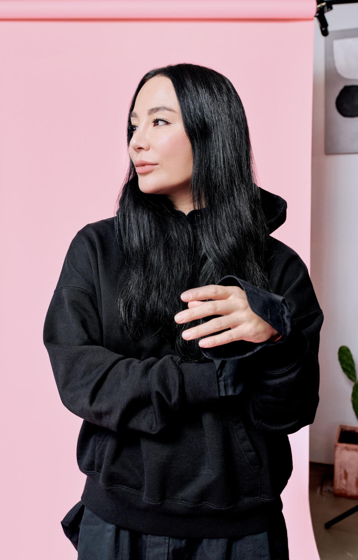 Woman in black hoodie standing looking to the side