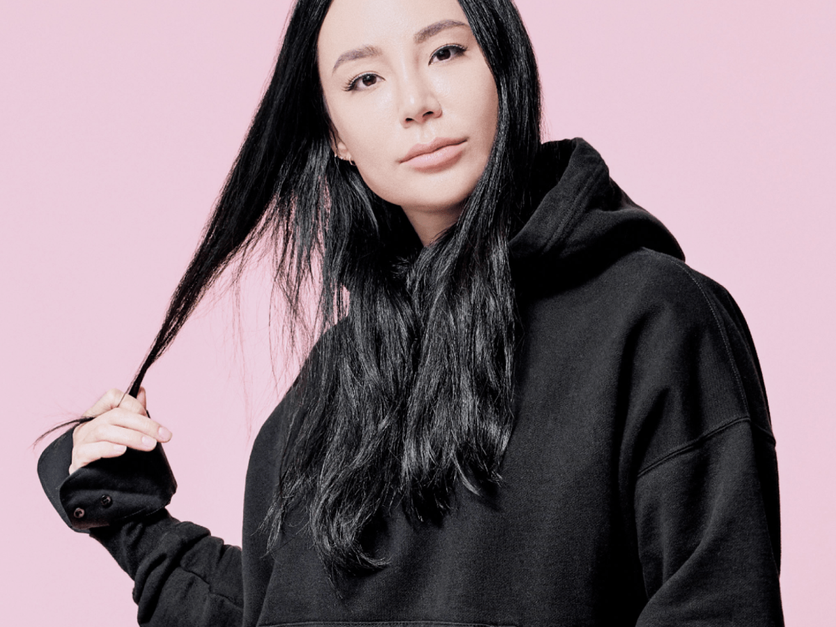 Woman in black hoodie playing with her hair and looking at the camera