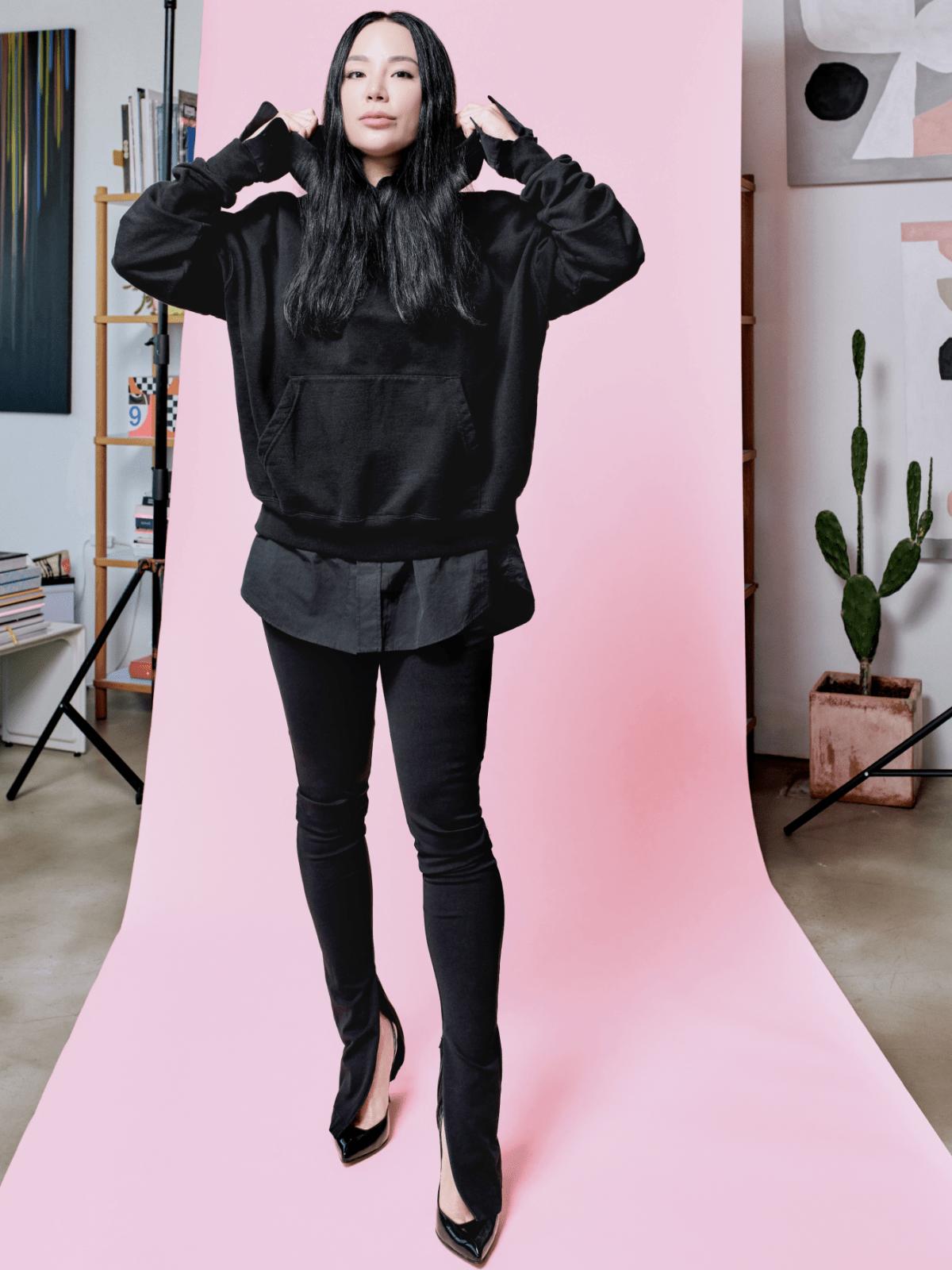 Woman standing pulling up the hood of her sweatshirt