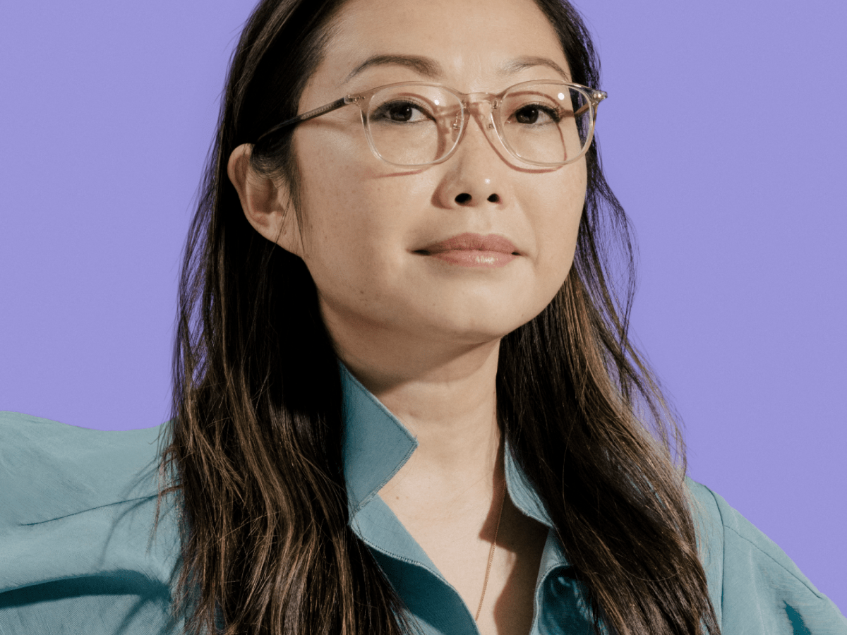 Woman in glasses and collared shirt looking at camera
