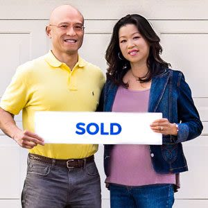 A couple smiling in front of their home after they just sold their house with a top realtor recommended by SoldNest