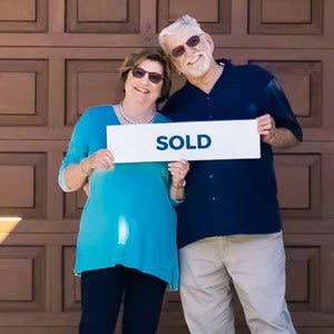 SoldNest clients holding a sold sign after selling their home for top dollar with a top realtor
