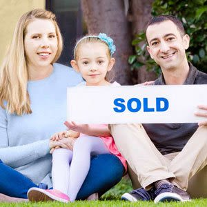 A family holding a real estate sold sign after selling their home fast with a top realtor