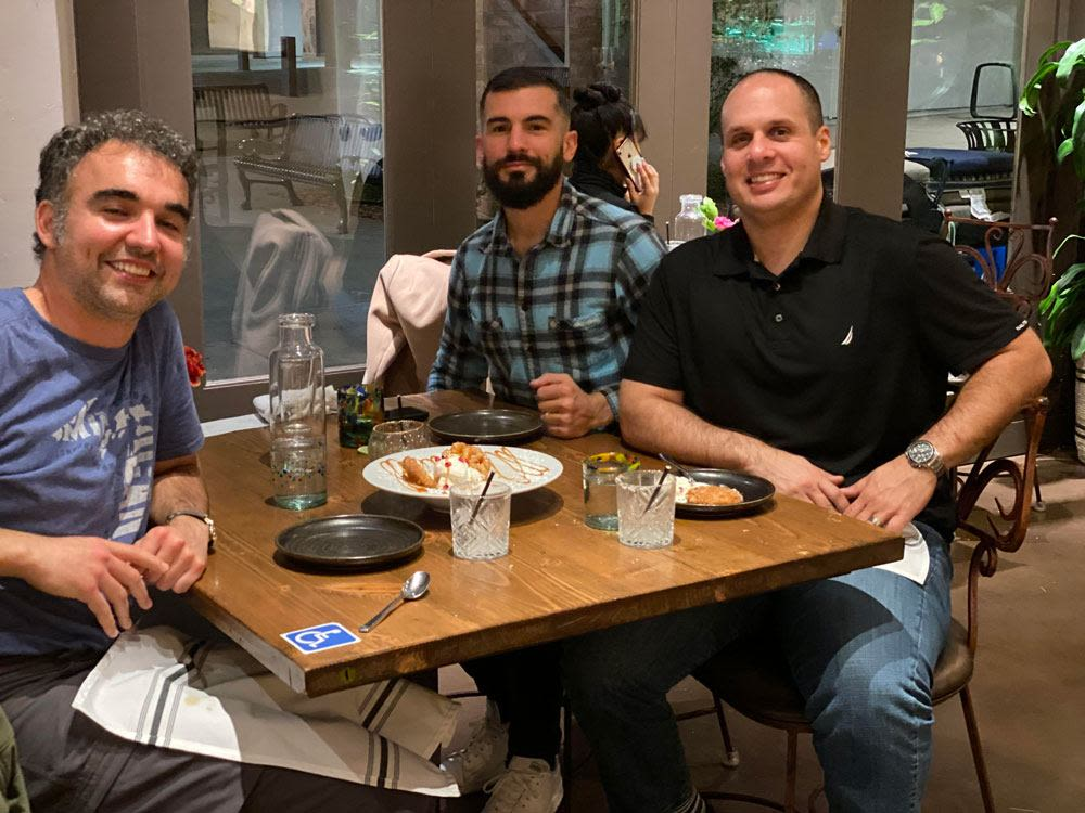 Founders of SoldNest sitting at a table smiling while eating dinner at a restaurant.