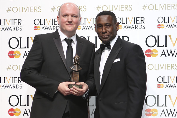 Mike Bartlett, winner of the Best New Play Award for King Charles III, at the 2015 Olivier Awards with presenter David Harewood. Photo by Pamela Raith.