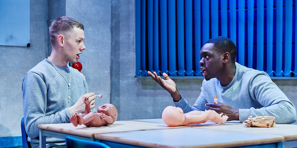 Joshua Finan and Ivan Oyik sat at a table together with toy baby dolls in Samuel Bailey's Shook