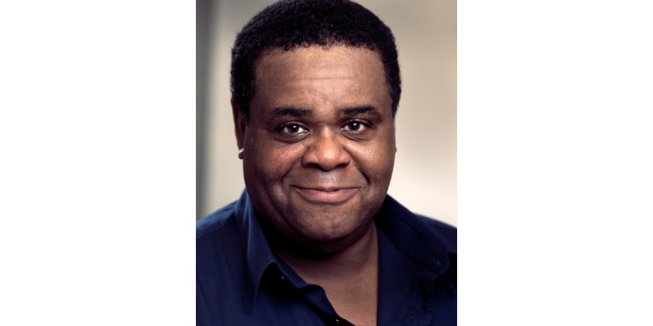 Close up photo of Clive Rowe wearing a navy shirt