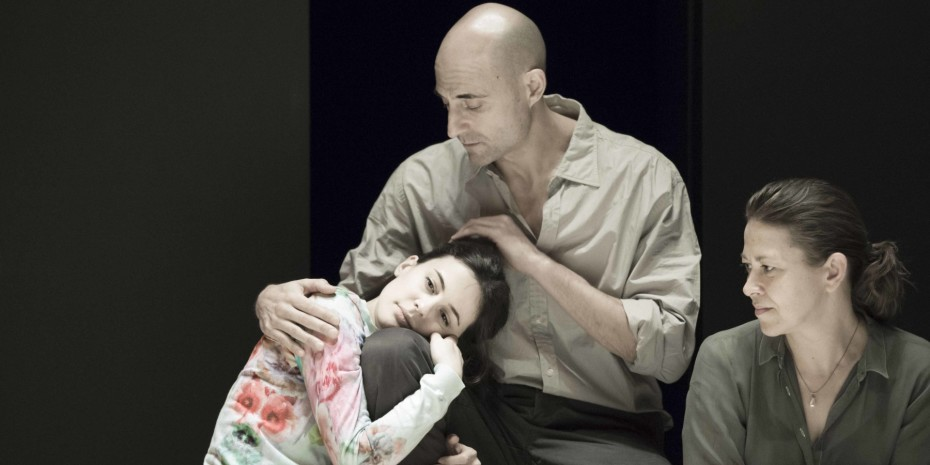 Phoebe Fox is being held by Mark Strong with Nicola Walker sat next to them.