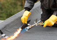 Een dakwerker bezig met dakbedekking