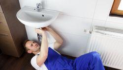 Loodgieter in blauwe overall die waterleiding repareert
