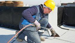 Dakwerker legt dakbedekking plat dak