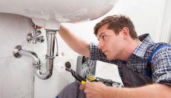Loodgieter repareert de lekkende waterleiding van de wastafel