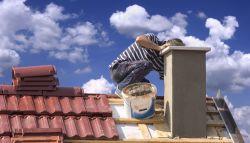 Man die schoorsteen plaatst op schuin dakpannen dak