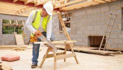 Schrijnwerker die hout zaagt in bouwplaats
