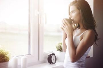 Vrouw kijkt uit pvc ramen