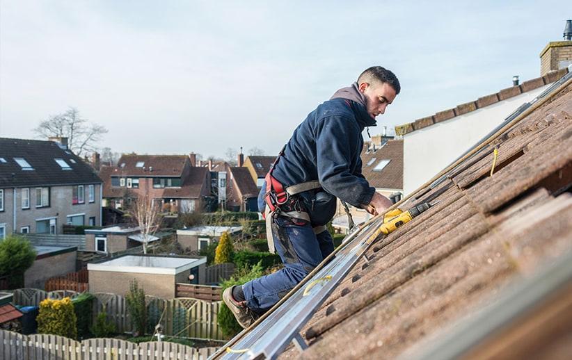 Zonnepanelen installateur op het dak