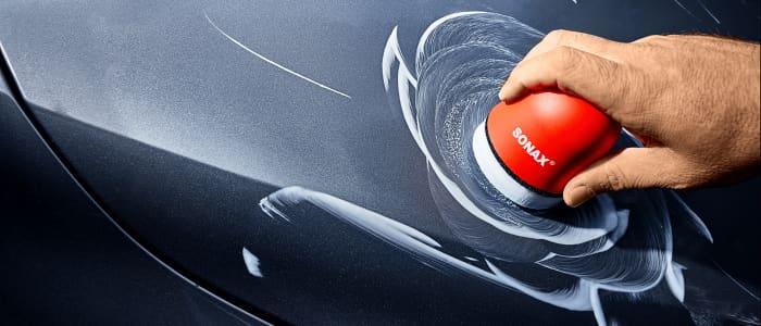 Person poliert eine Autotür