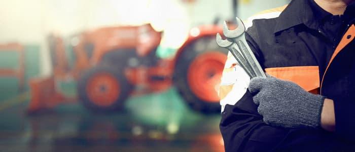 Mann mit Schraubenschlüsseln in der Hand steht vor einem Traktor