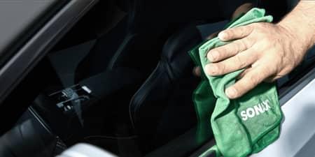 Person reinigt Lenkrad mit einem Schwamm