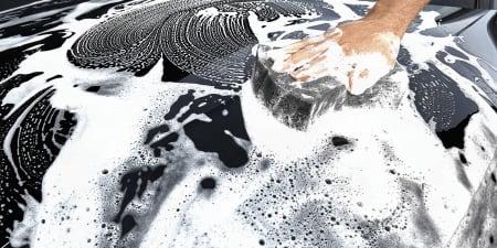 Person reinigt Motorhaube mit einem Shampoo
