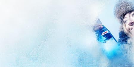 Frau enteist eine Windschutzscheibe