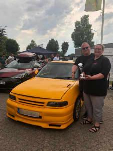 Tuner mit Award neben ihrem Auto