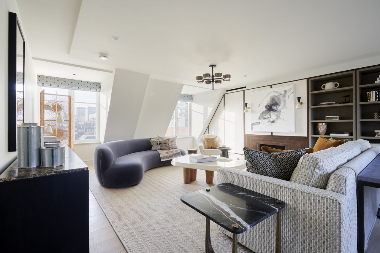 Interior living room of a modernly furnished serviced apartment in London; curved blue couch, white coffee table, and seating.