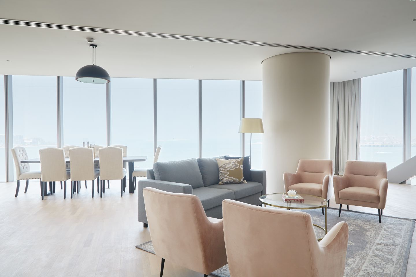 Living room & dining room of a serviced apartment in Dubai with floor to ceiling windows.