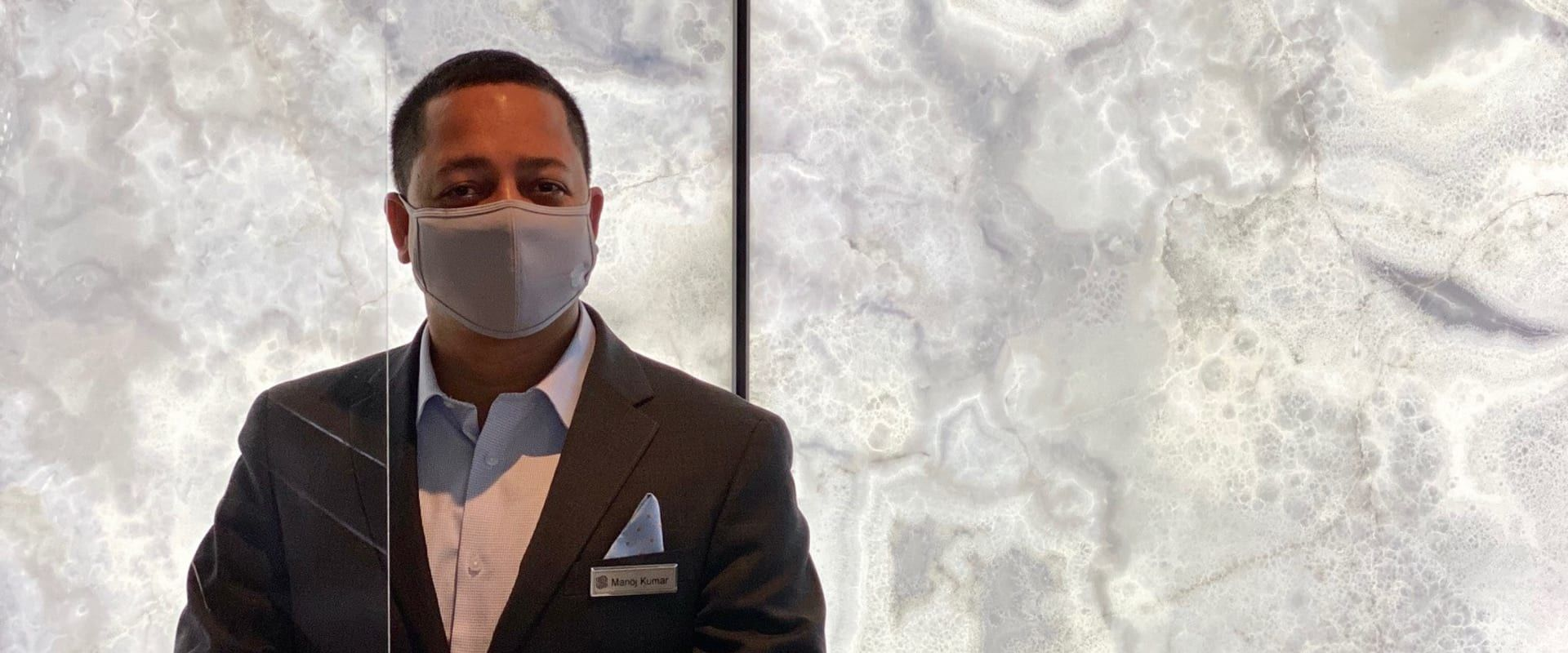 Employee at front desk with mask