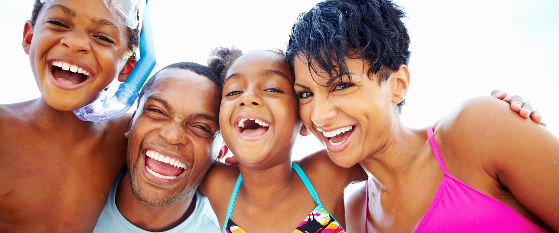 Family laughing while posing in swimsuits