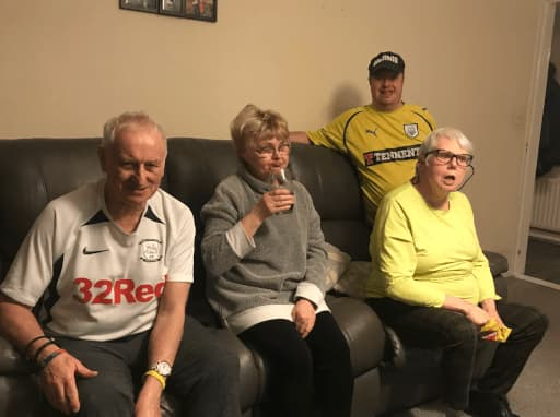 Two males and two females sitting on a sofa socialising