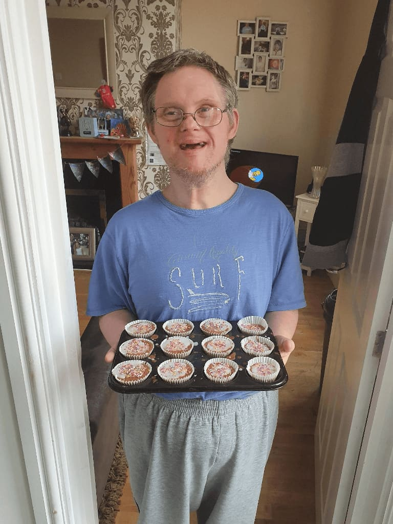 A male holding cupcakes they have baked