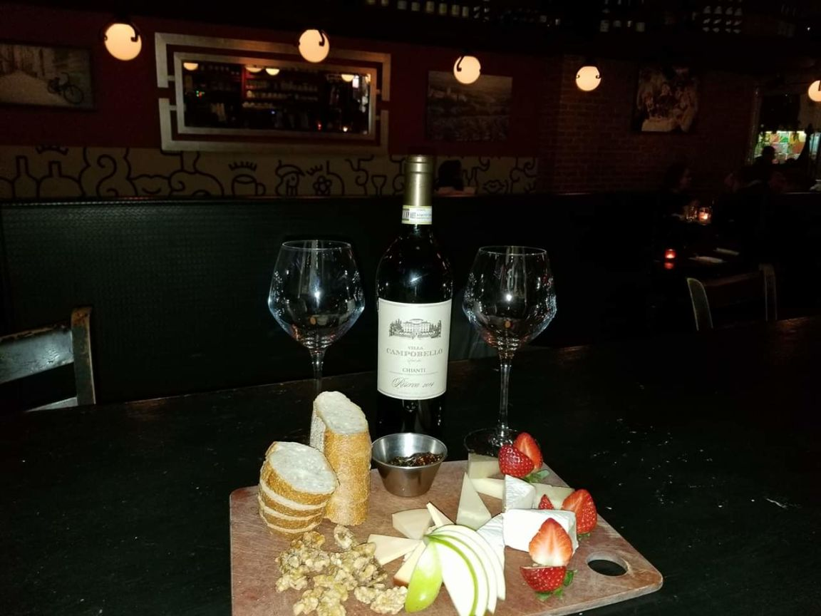 a table with a bottle of wine, glasses and food