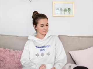 Frau sitzt auf der Couch mit einer Tasse Tee und trägt ein personalisierten Hoodie