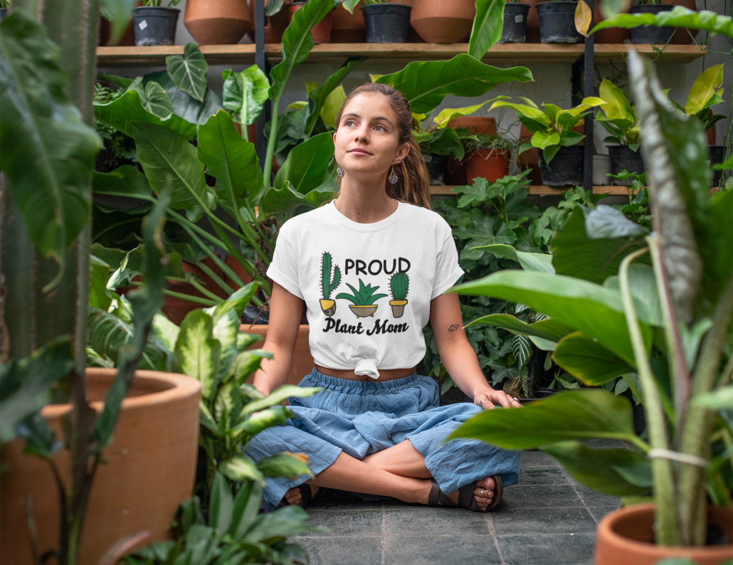 Frau sitzt zwischen Pflanzen und trägt ein selbstgestaltetes T-Shirt
